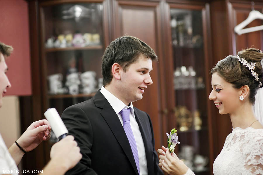 The bride and the groom help each other getting ready in their wedding day.