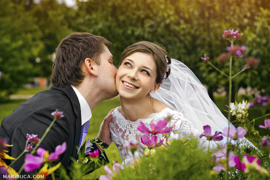 The groom kisses the bride surrounded the green garden and pink flowers in the front of them.