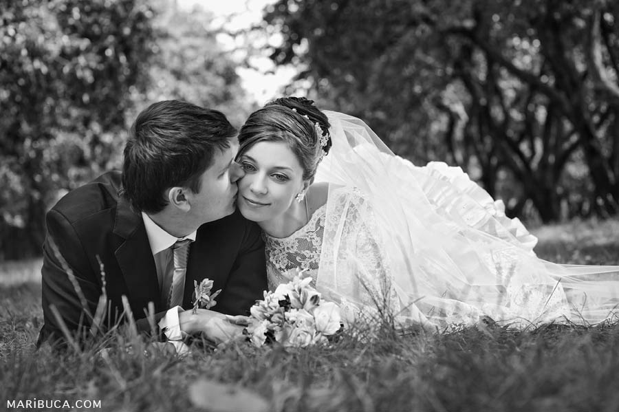 Black and white image where bride and groom lay down on the grass and relax.