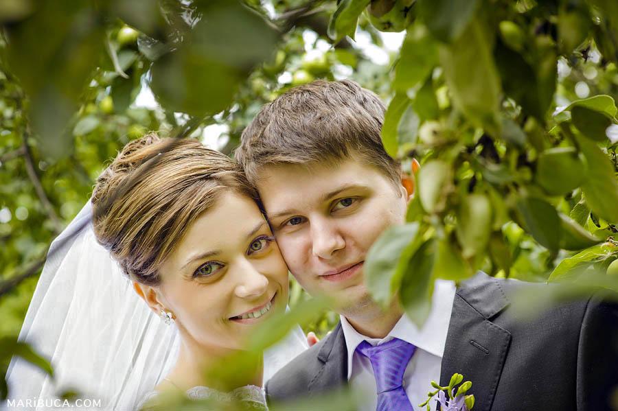 Bride and groom portrait in the apple green garden