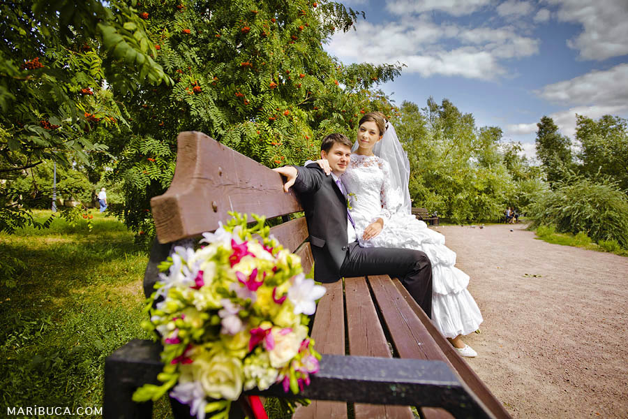 The bride and groom are sitting on a brown wooden bench against the background of a wedding colored bouquet and green trees around.