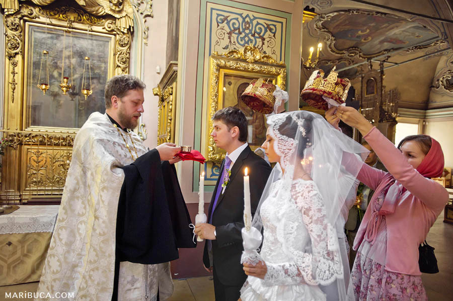 Traditional Christian wedding ceremony in a church. Father gives a drink sip of wine in a Christian church