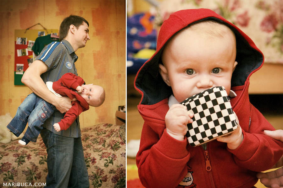 Dad carries baby son on his hands on the background of orange wallpaper. A six month old baby in a red hood is wearing a red hoodie