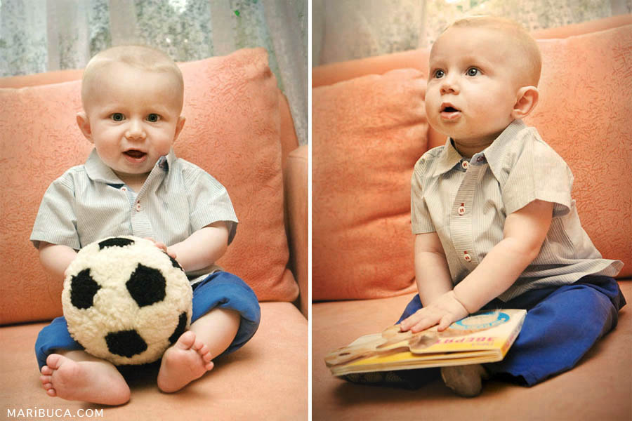 Six month the baby is sitting in the peach color sofa and holds soccer ball and the book.