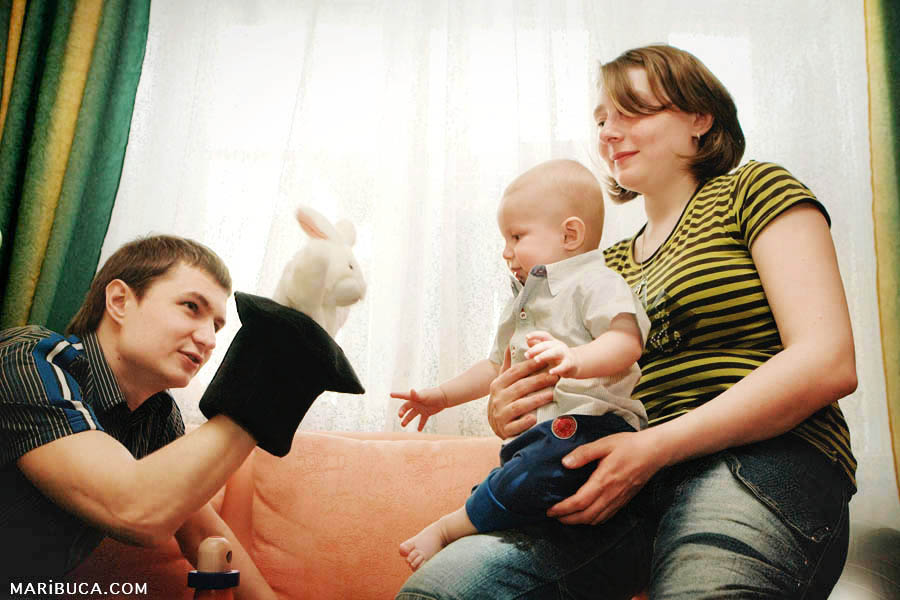 Parents play with six month old son at home.