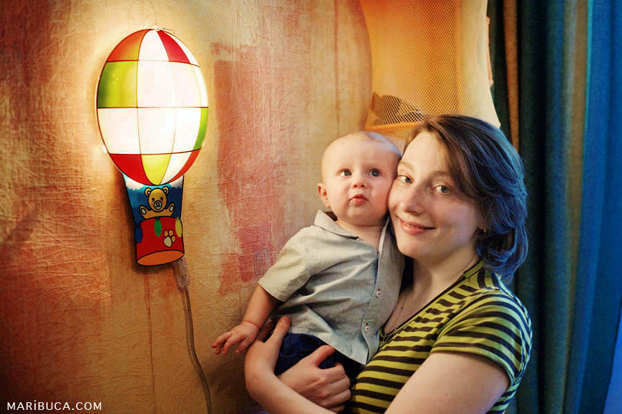 In the cozy house with orange paper wall, the mother holds her six month old the son.