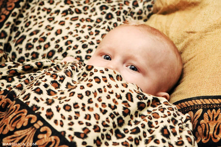 The baby lay down in the bad with brown leopard pattern.
