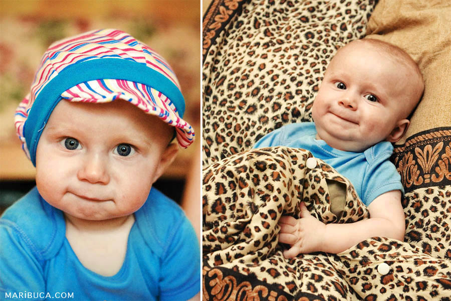 Portrait of the baby in the light blue clothes and colored hat with blue trim in the leopard blanket.