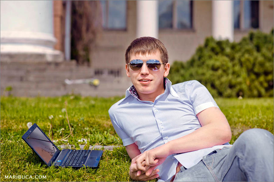 Portrait of the guy in the sunglasses who lays down in the green grass in the garden.