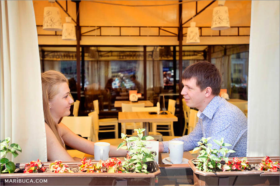 The couple looks each other in the coffee shop in the engagement photo session.