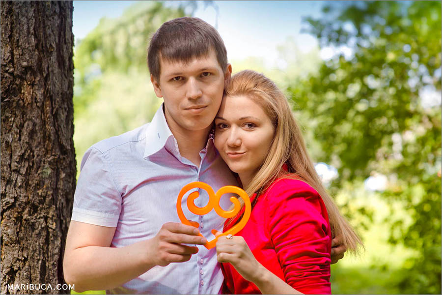 Fiancee and fiance hug each other and hold the orange wooden heart.