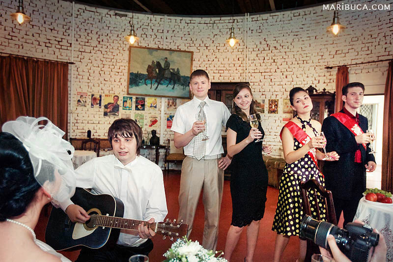 the groom plays the guitar and sings a song for his bride and the bridal party dances to the music