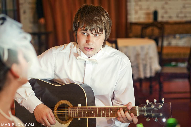 the groom plays the guitar and sings a song for his beautiful bride in the room