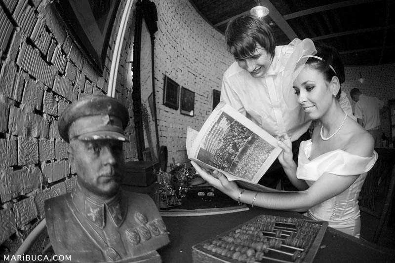 The bride and groom read the new newspaper surrounded by the Soviet time of the 1940s