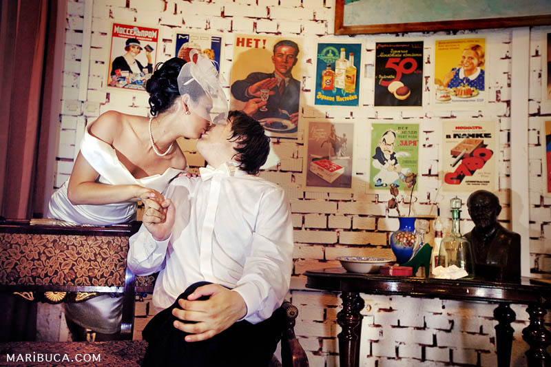 Bride and groom are kissing each other and in the background old posters Soviet times