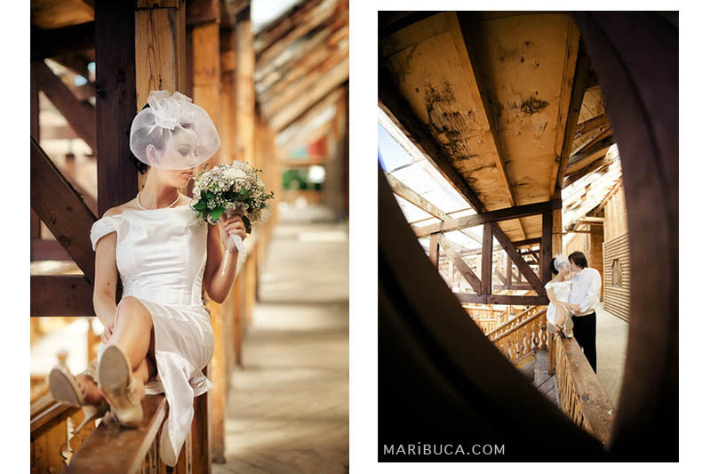 Portrait of the bride with elegant white short veil hat smells her bouquet. The newlyweds couple are kissing each other in the old wooden construction place.