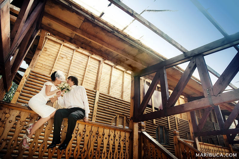 The bride and groom look each other and almost kiss each other in the brown wooden background