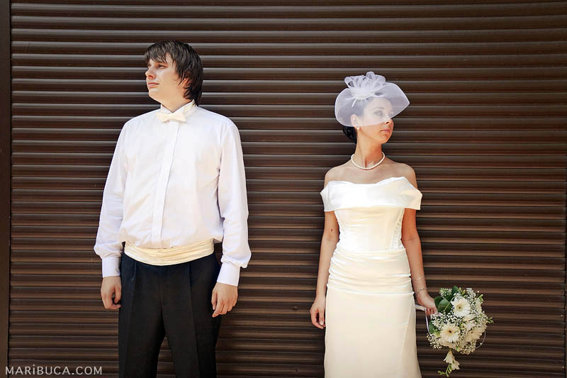 The bride and groom look in different directions on the background of brown metal gates