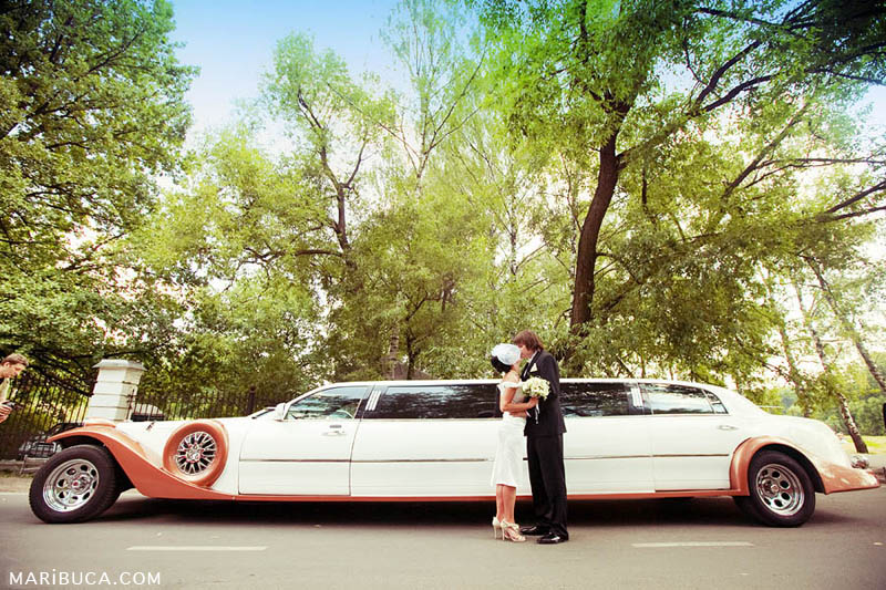 The bride and groom are kissing each other and they stay in front of the white long limo with orange insert around wheels.