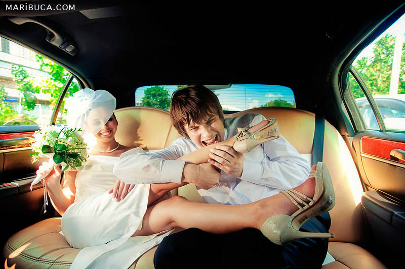 The groom try to bites his bride leg inside the limo with yellow seats