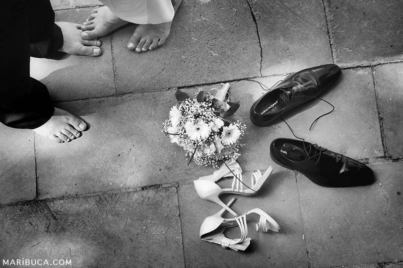 Newlyweds with bare feet and wedding bouquet and shoes lay down in the concrete.