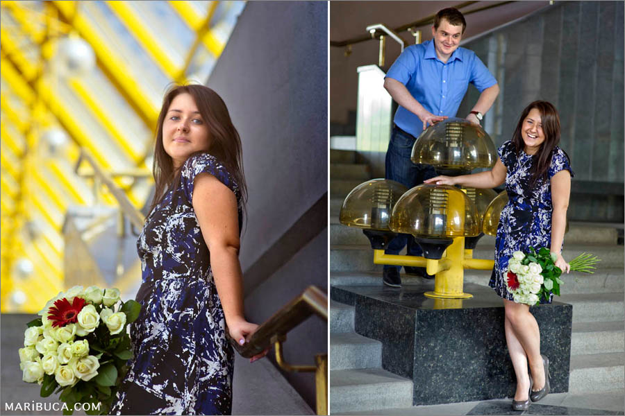 Portrait of the girl with the white roses and yellow and gray background. Couple in the blue clothes have fun in the engagement photo-session.