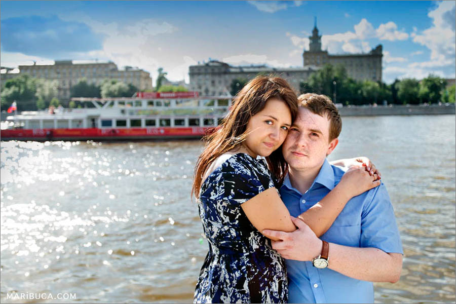 boy and girl hugging each other on the background of the river steamer