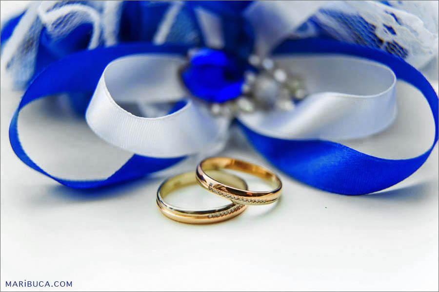 Golden wedding rings and white-navy garter in the white background