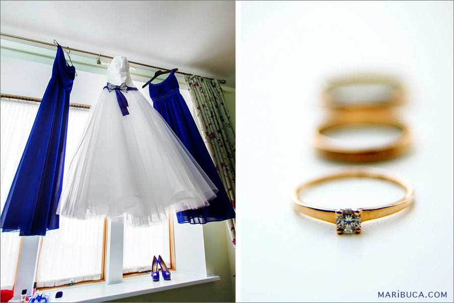 White wedding dress and navy blue bridesmaids dresses hanging up against the window. Yellow golden wedding band.