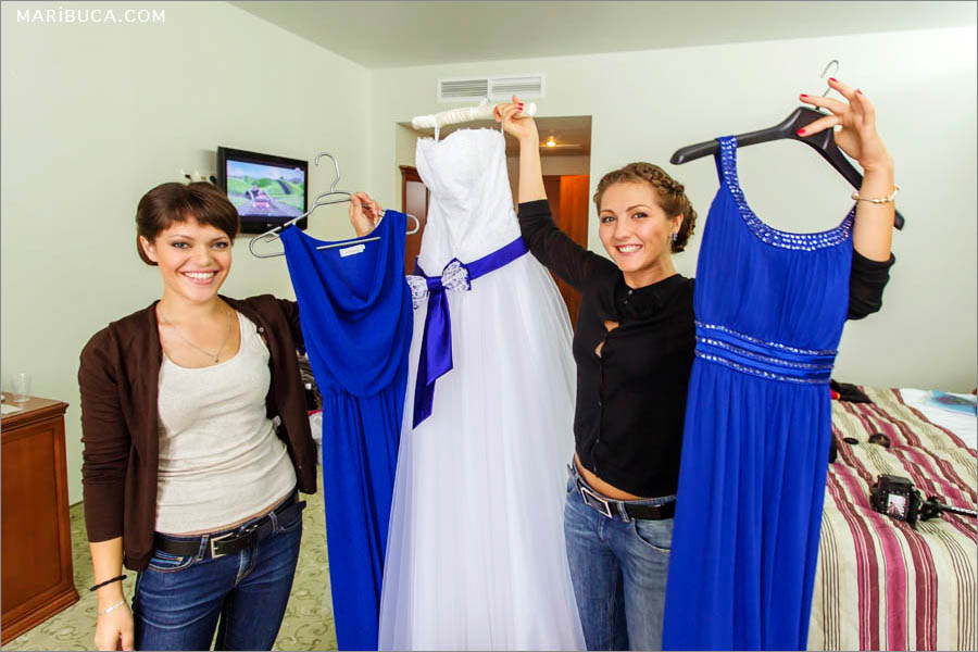 Bridesmaids hold own navy blue dresses and white wedding dress the bride.