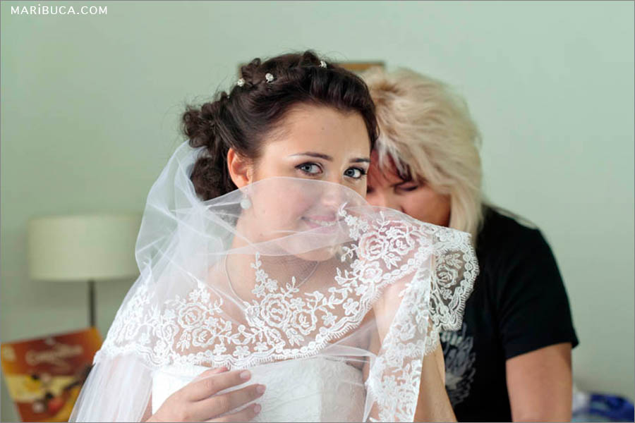 Mom helps daughter to put the wedding dress in the hotel