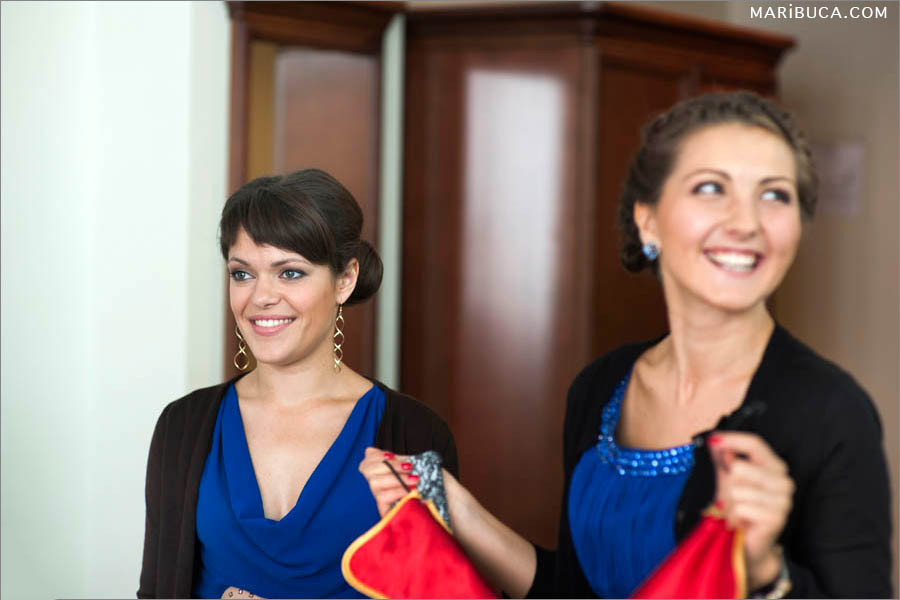 Bridesmaids laughing and wear navy blue dresses.