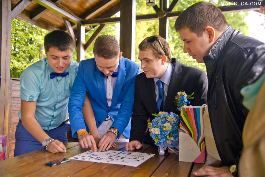 The groomsmen and groom try to unraveling puzzle before they can to see the bride.