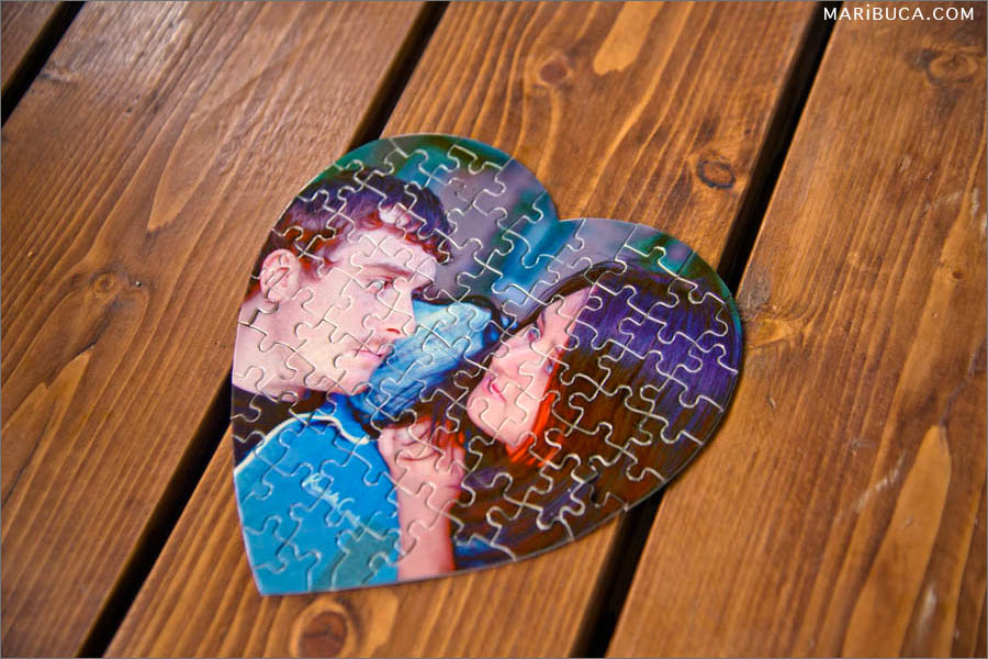 Photo of a bride and groom in the form of a heart from a puzzle, lying on a brown wooden table.
