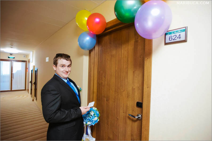 The groom stays in front the door with different color balloons and he wait next step to see his gorgeous bride.