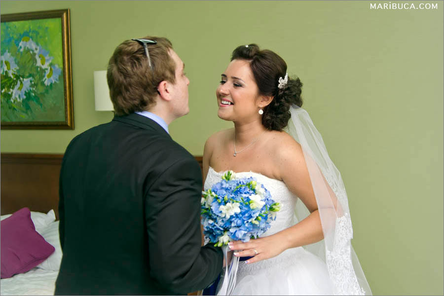 The groom and bride try to kiss each other after first look in the Hilton hotel, Santa Clara.