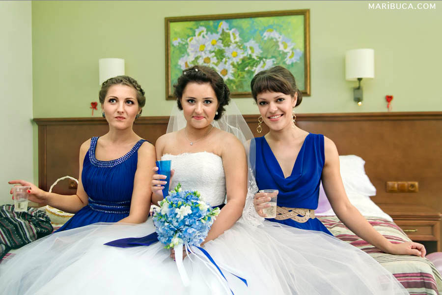 Bridesmaids are sitting around the beautiful bride who holding white-blue wedding bouquet in the Hilton hotel, Santa Clara