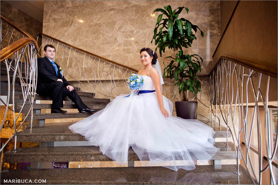 Bride and groom sitting in the staircases in the Marriott, Santa Clara