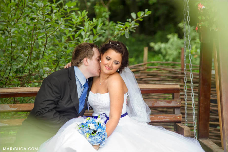 Bride and groom are kissing each other and sitting in the swinging bench in the park.