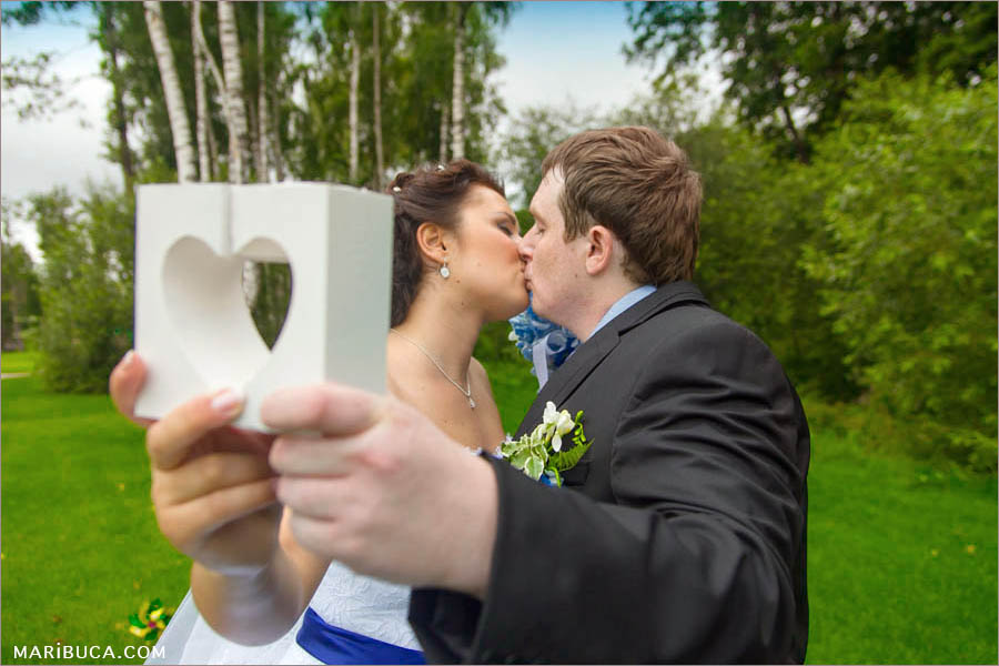 the bride and groom hold each their half white hearts and kissing each other in the park