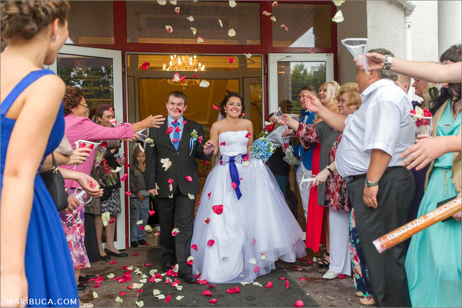 guests throw red and white rose petals when newlyweds leave the registry office in the San Jose.