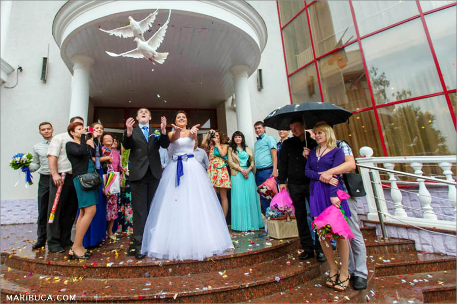 newlyweds release pigeons and stays outside the register office in the rainy day