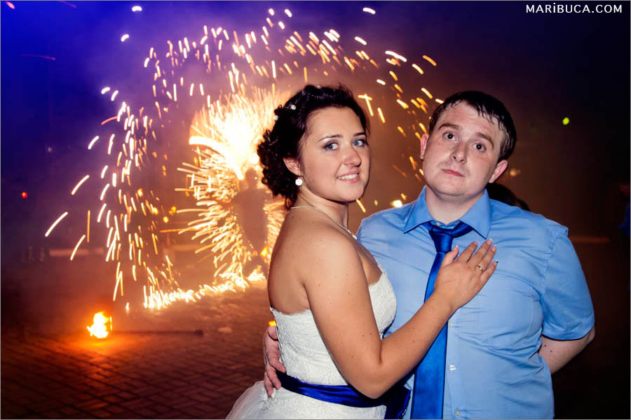 Bride and groom a little bit tired but so happy in their special wedding day with fireworks