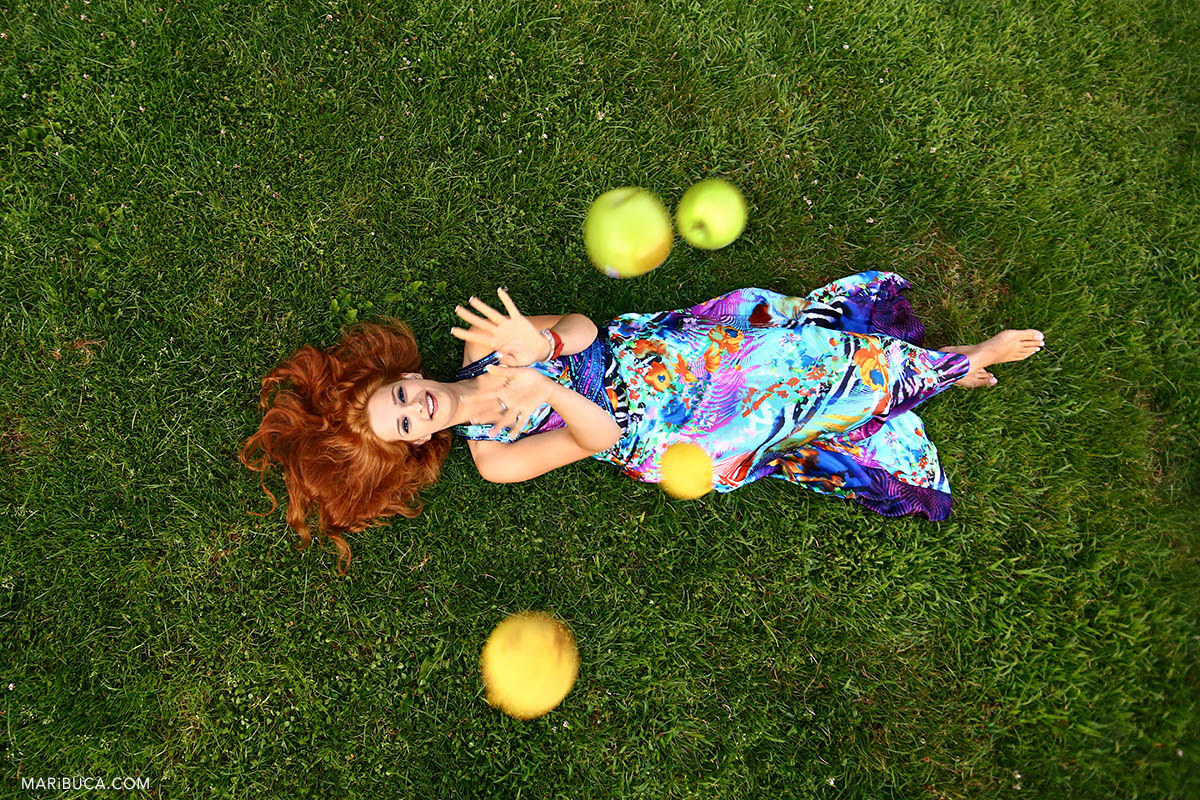 The girl with red hair and a colored dress lies on her back on the green grass and throws green apples