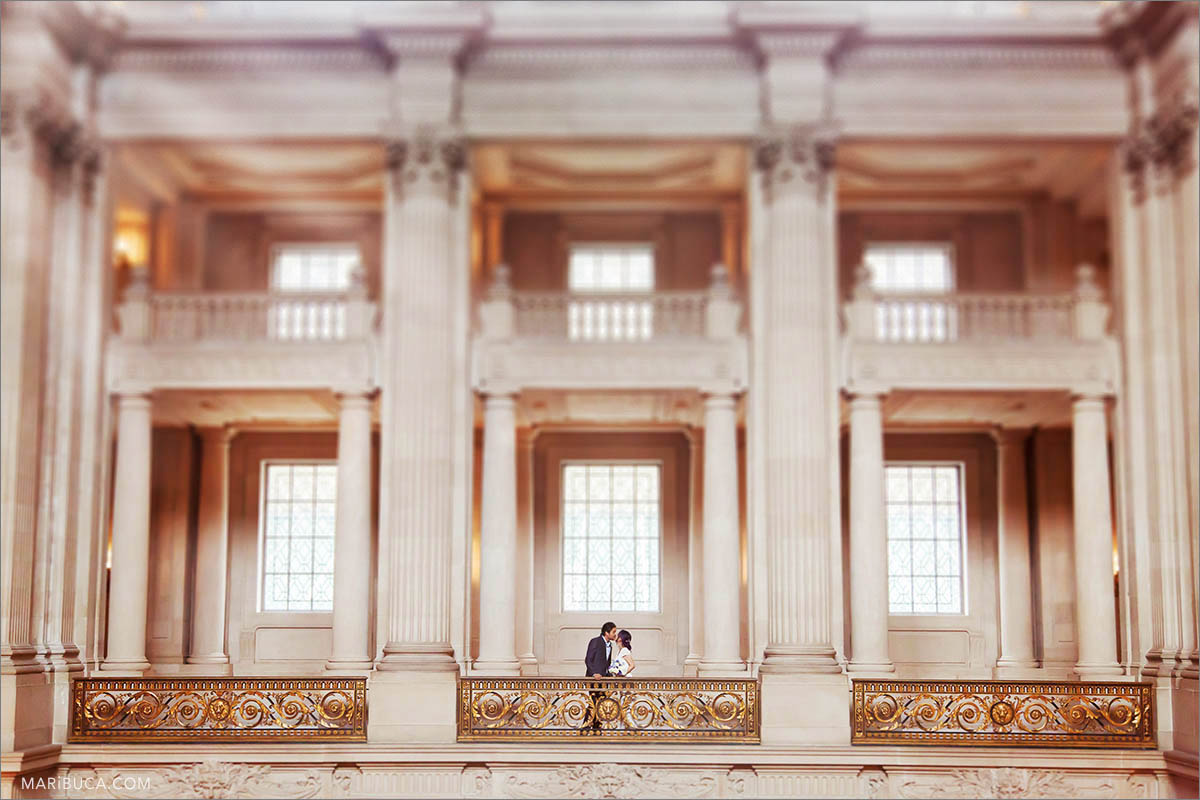 The bride and groom kiss on the second floor of San Francisco City Hall early in the morning