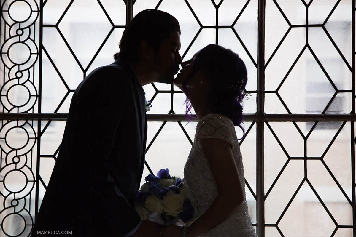 The newlyweds in the black and white color are kissing each other in the light background, San Francisco City Hall, California