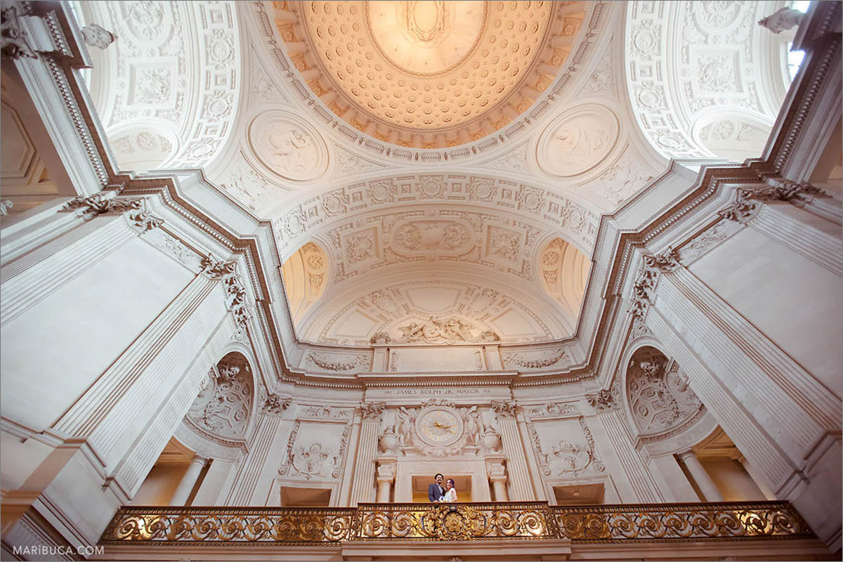 The beautiful architecture of the San Francisco City Hall inside and newlyweds couple.