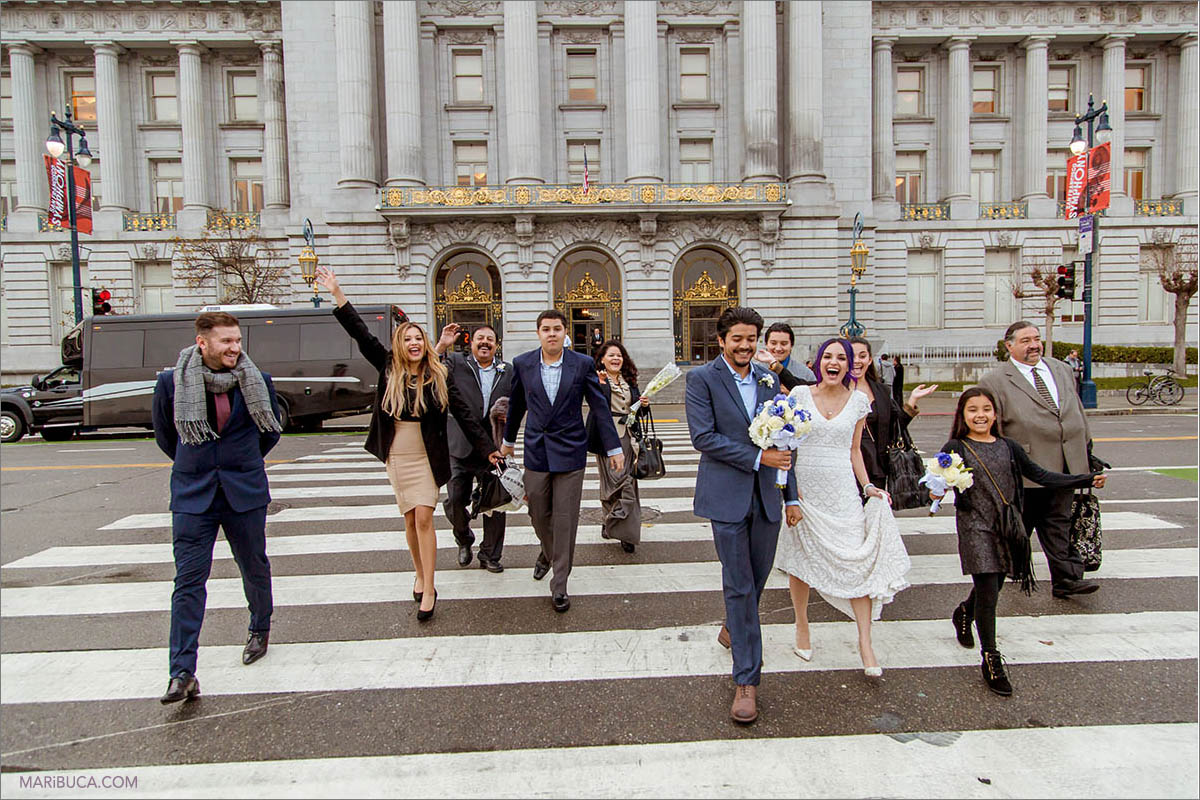 The bride and groom with friends excited after wedding ceremony in the San Francisco City Hall.