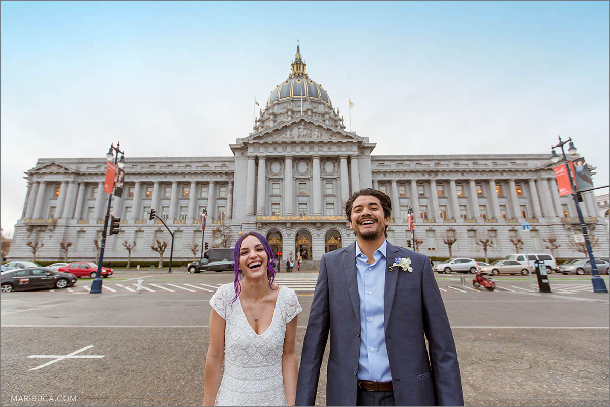 The bride and groom are laughing in the background of the San Francisco City Hall, California.