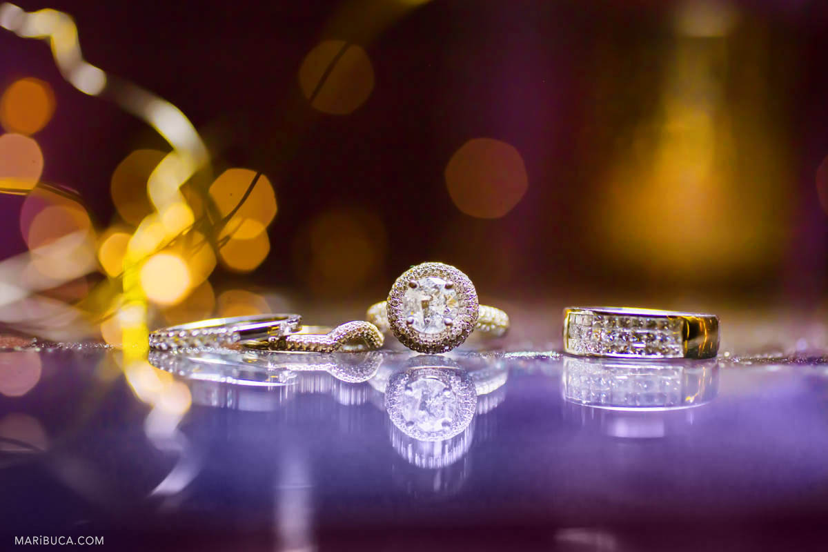 Wedding rings and an engagement ring - purple and yellow background